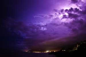 Lightning bolts above tropical beach in Hawaii.