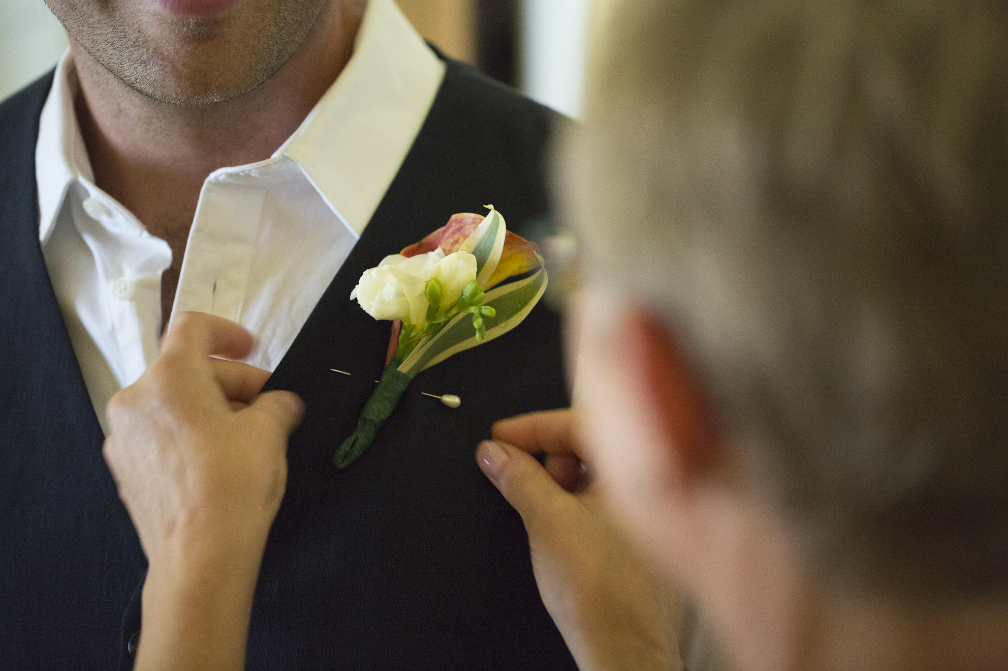 Mother puts flowers on groom